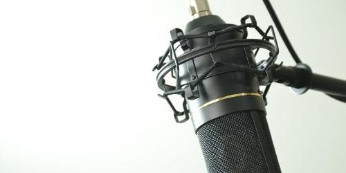 Podcast: Ein modernes Mikrofon vor weißem Hintergrund